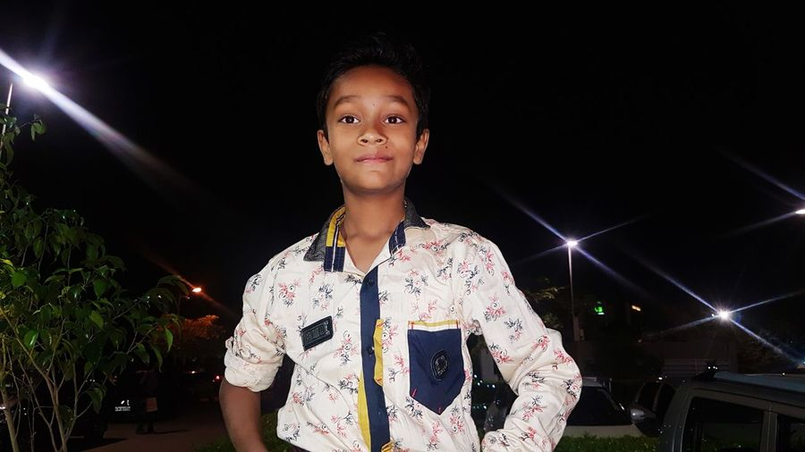 Portrait of smiling boy standing against sky at night