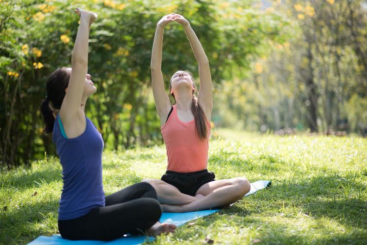 Girls doing yoga in park