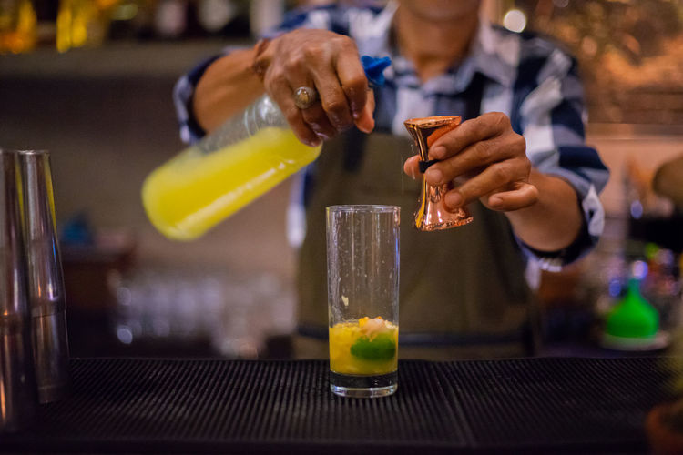 Midsection of bartender preparing drinks while standing in bar