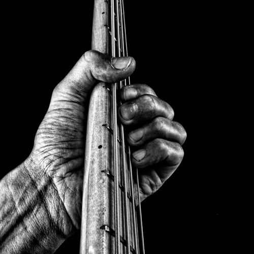 Cropped Image Of Guitarist Playing Bass Guitar Against Black Background