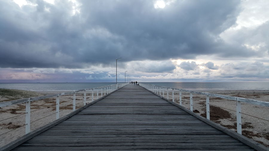 Pier Over Beach Leading Towards Sea Against Cloudy Sky