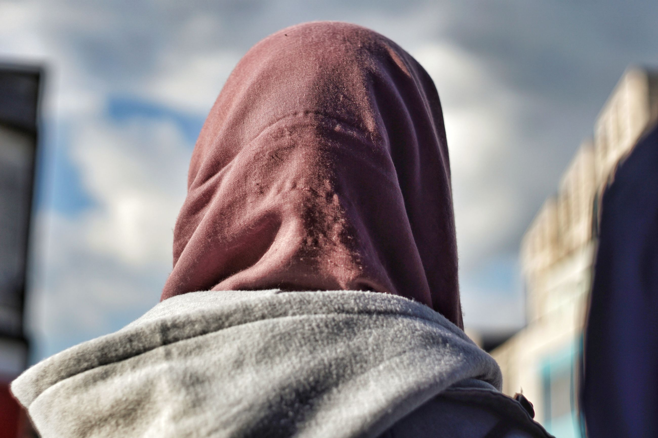 one person, real people, headshot, hood, human body part, men, hood - clothing, body part, day, lifestyles, portrait, rear view, clothing, selective focus, unrecognizable person, cloud - sky, hooded shirt, focus on foreground, sky, outdoors, obscured face, human face