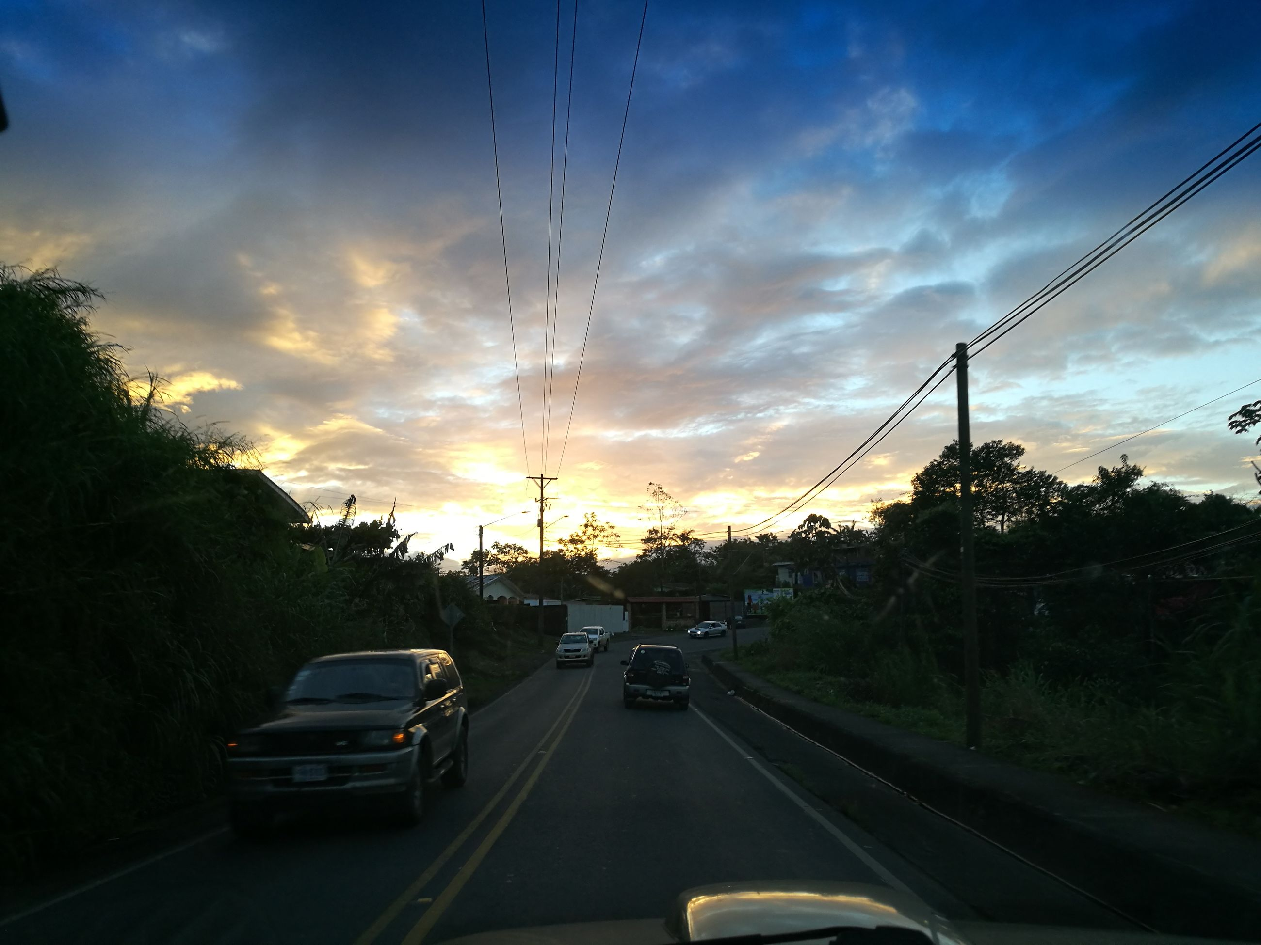 car, transportation, sunset, tree, road, mode of transport, sky, the way forward, street, land vehicle, traffic, cloud - sky, no people, palm tree, city, outdoors, nature, architecture, day