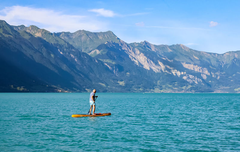 Man in a blue lake against mountains