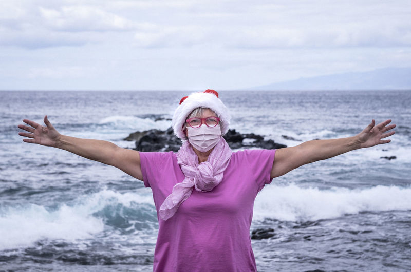 Portrait of senior woman wearing mask with arms outstretched standing against sea