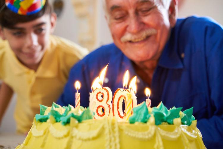 Senior man looking cake during birthday celebration