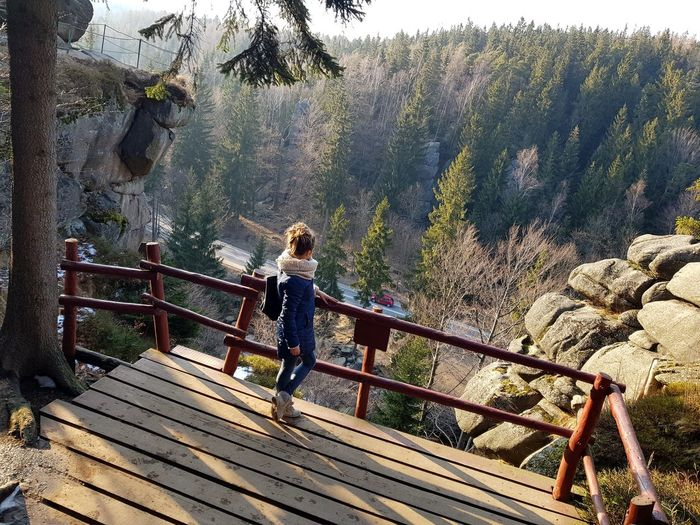 Side view of young woman standing on observation point in forest