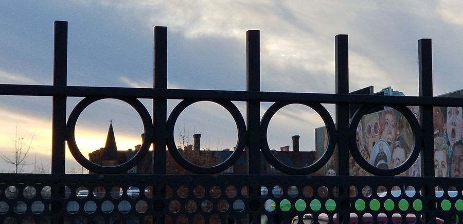 View through fence Mural Art Mural Cincinnati Performing Arts Clouds Clouds And Sky Sunset City Politics And Government Cityscape Sunset Winter Wrought Iron Bridge - Man Made Structure Politics Urban Skyline Steel Metal Grate Iron - Metal Fence Boundary