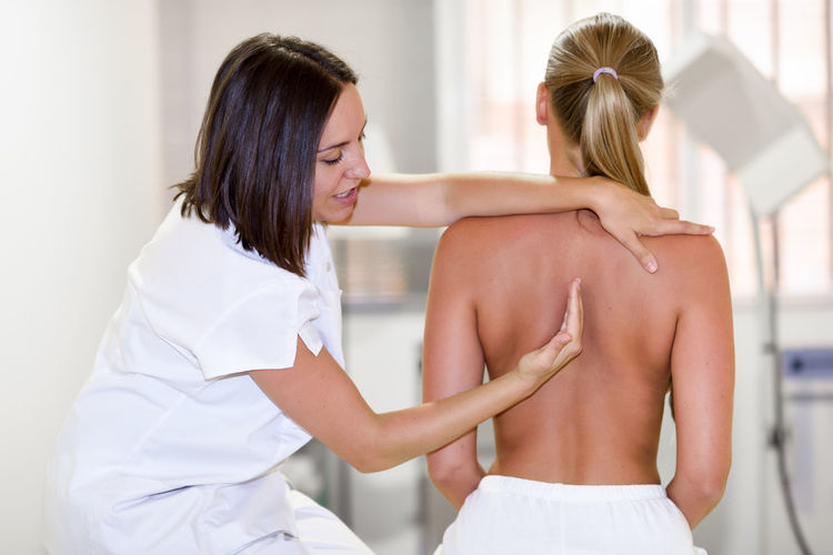 Physiotherapist Examining Female Patient
