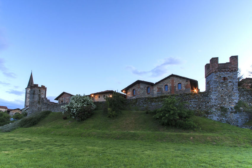Candelo, Biella - May 4, 2016: Panoramic view of the Medieval village of Ricetto di Candelo in Piedmont, used as a refuge in times of attack during the Middle Age. Architecture Biella Blue Building Exterior Built Structure Candelo Candelo In Fiore Day Exterior Field Grass Grassy Green Color Growth Hill House Italy Landscape Medieval Village Nature No People Outdoors Residential Structure Ricetto Di Candelo  Sky