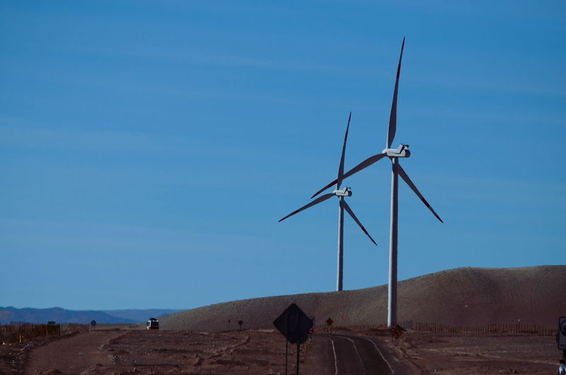 Wind turbines on desert against clear blue sky