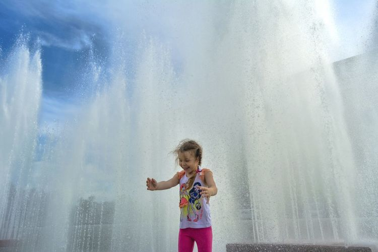 Happy Girl Standing Against Fountain