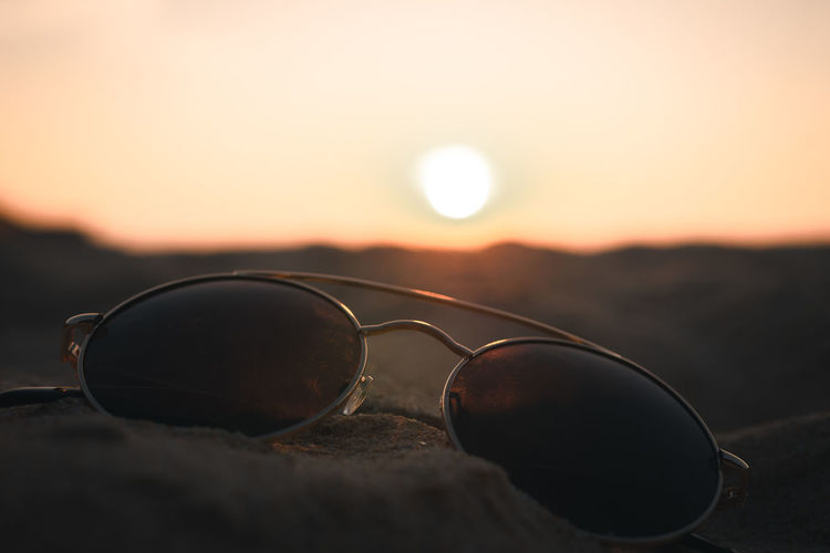 Close-up of sunglasses on street during sunset
