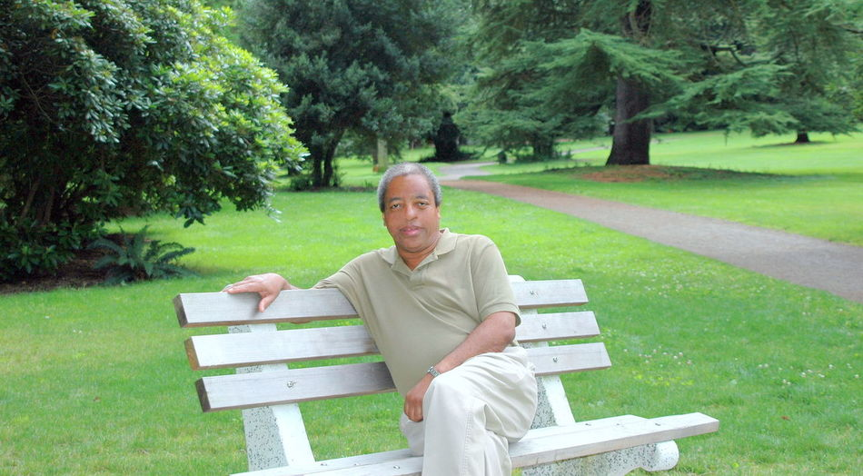 Portrait of a man sitting on bench in park