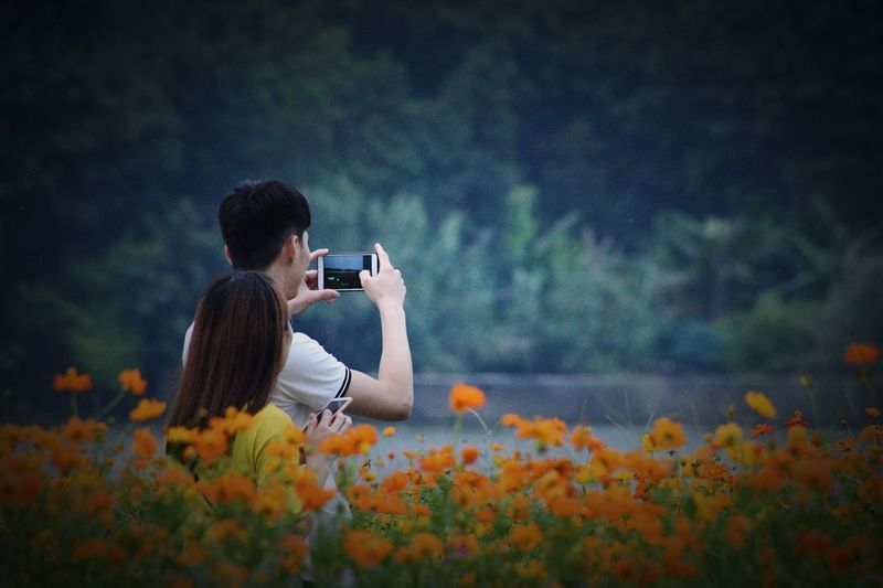 Couple photographing with mobile phones while standing by flowers