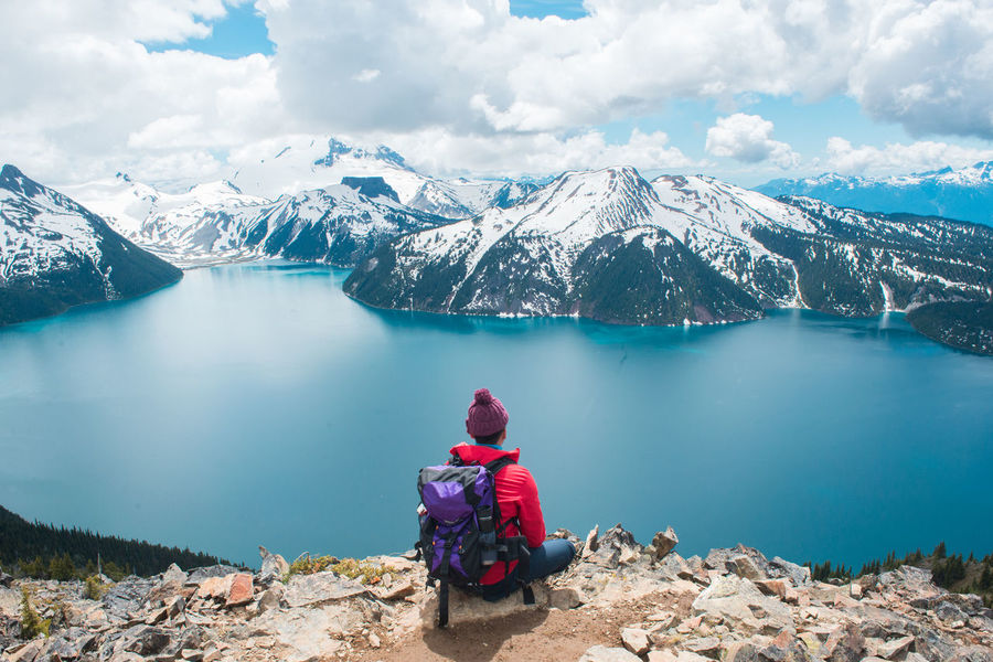 Garibaldi Lake Panorama Ridge Beauty In Nature Canada Cloud - Sky Cold Temperature Lake Leisure Activity Looking At View Mountain Mountain Range Nature Non-urban Scene One Person Outdoors Real People Rear View Scenics - Nature Sitting Snow Snowcapped Mountain Tranquil Scene Water Winter