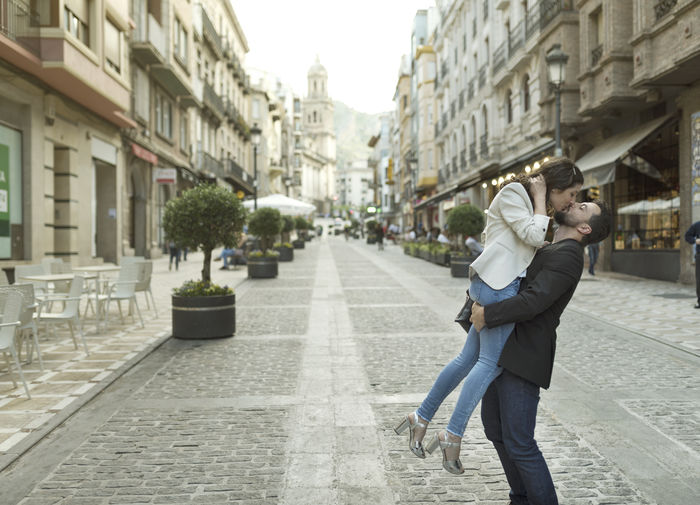Side view of man kissing woman while lifting her on street