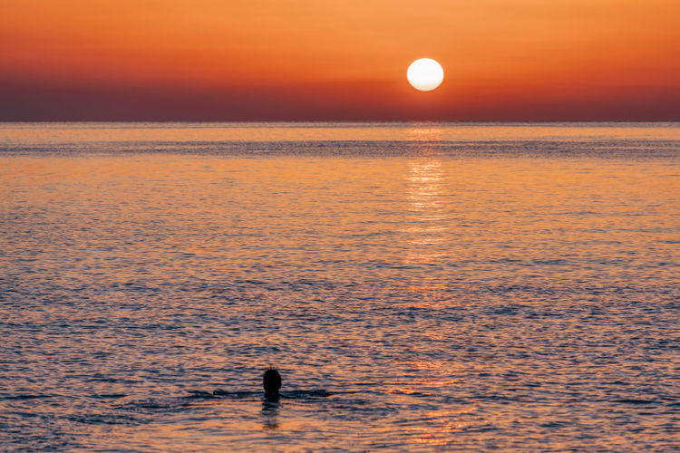 Silhouette person on sea against orange sky during sunset