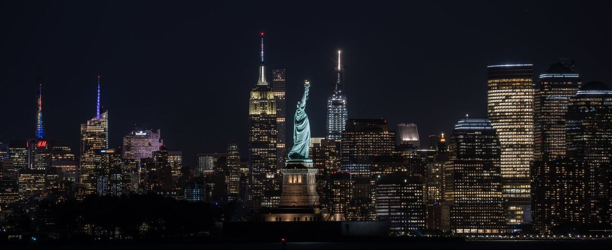 Illuminated buildings and statue of liberty in city at night