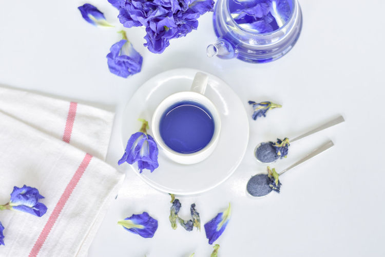 High Angle View Of Purple Flowers By Herbal Tea On White Table