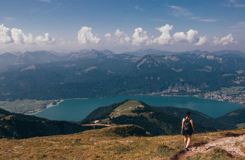 Woman in black sportswear and a small backpack with food meets famous austrian mountain schafberg