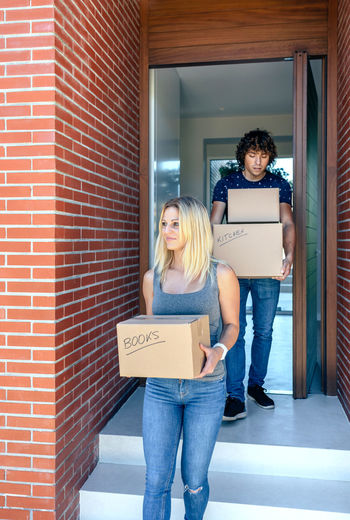 Happy couple moving carrying cardboard boxes to their new home Cardboard Box Collaboration Couple Entrance Happiness Home Household Man Moving Relationship Woman Young Boxes Caucasian Door Estate Female House Male Move New Home Partner Two People Vertical Weight