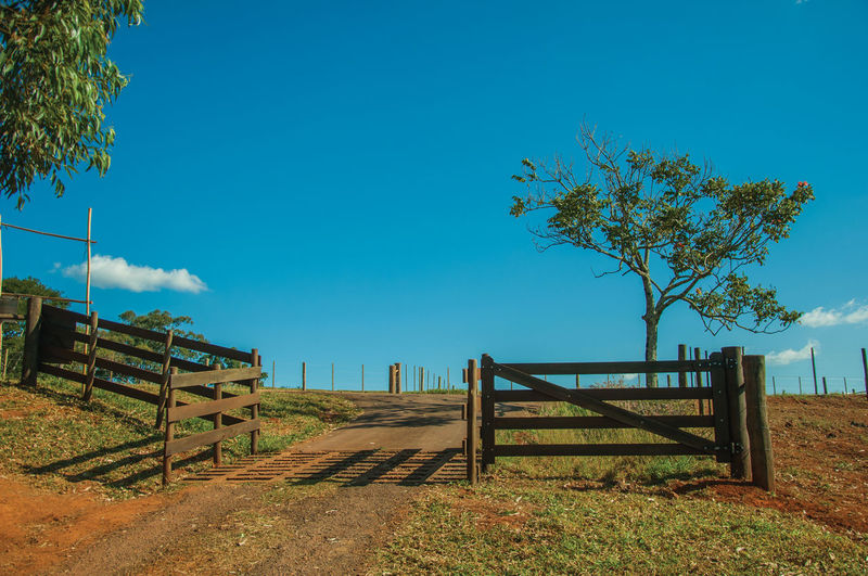 Fence on field against clear blue sky