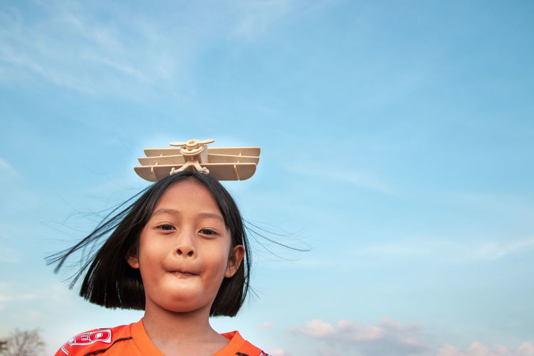 Low angle portrait of girl with model airplane on head against sky