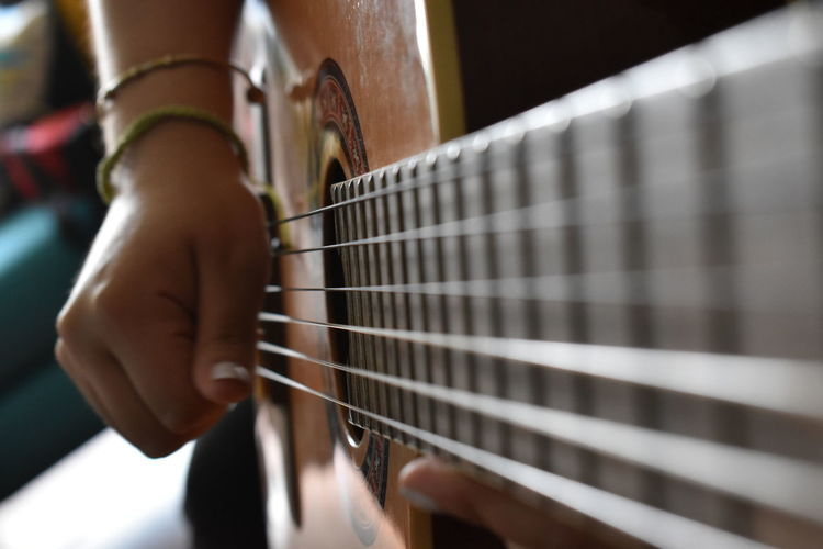 Cropped hand of woman playing guitar at home