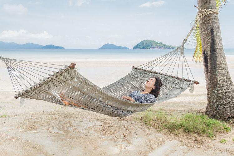 Man relaxing on hammock at beach against sky