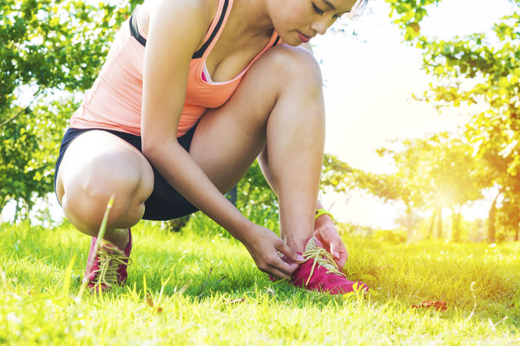 Young Woman Tying Shoelace On Grass
