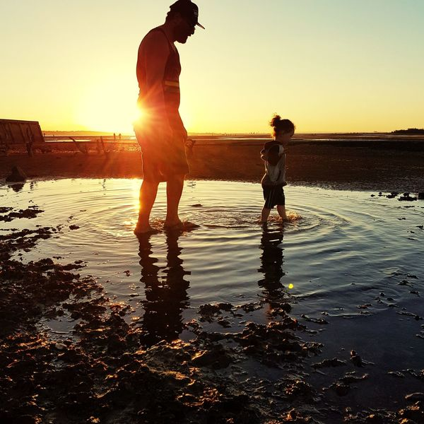 Father and son at sunset in a pool of water Full Length