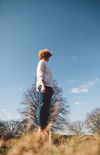 Full length of woman standing on tree trunk