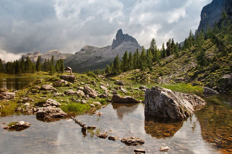 Scenic View Of Dolomites By Lake Against Cloudy Sky