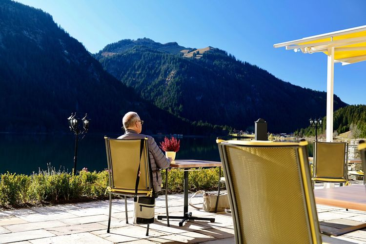 Rear view man sitting on chair by mountain range