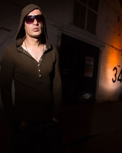 Portrait Of Serious Man Wearing Sunglasses While Standing Against Wall