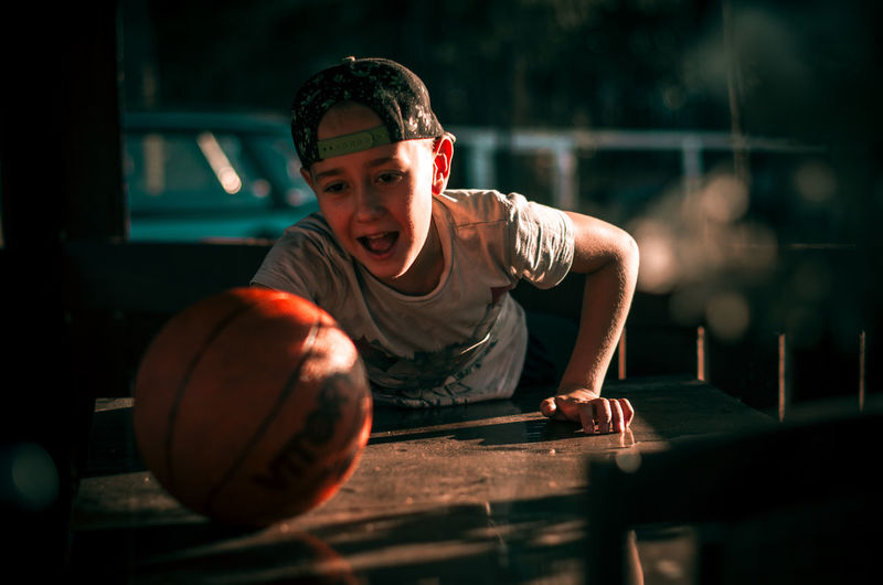 Portrait of boy with ball on table
