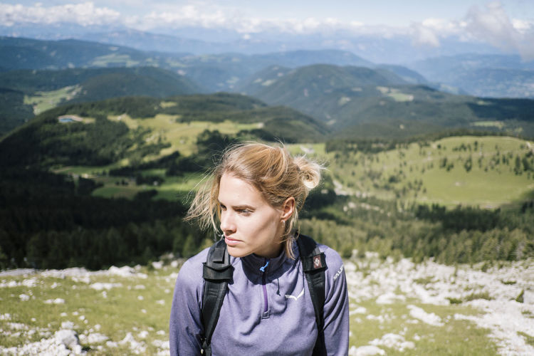Woman looking away while standing against landscape