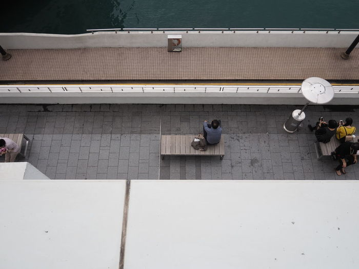 High angle view of people sitting on bench at sidewalk