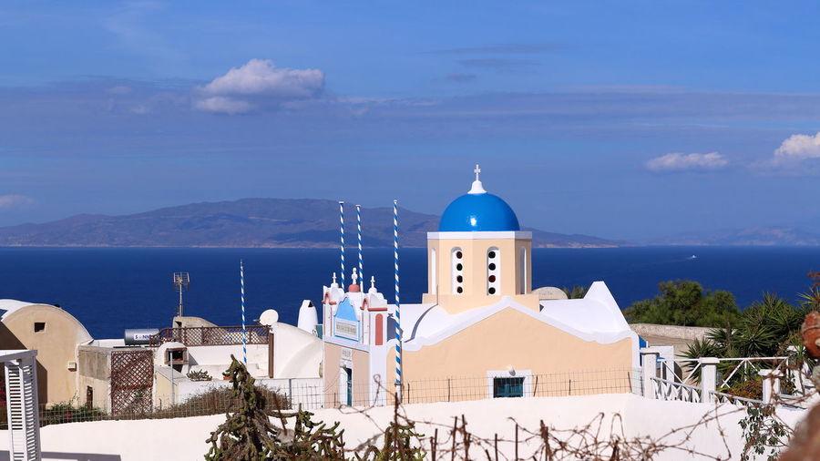 Church amidst buildings against blue sky