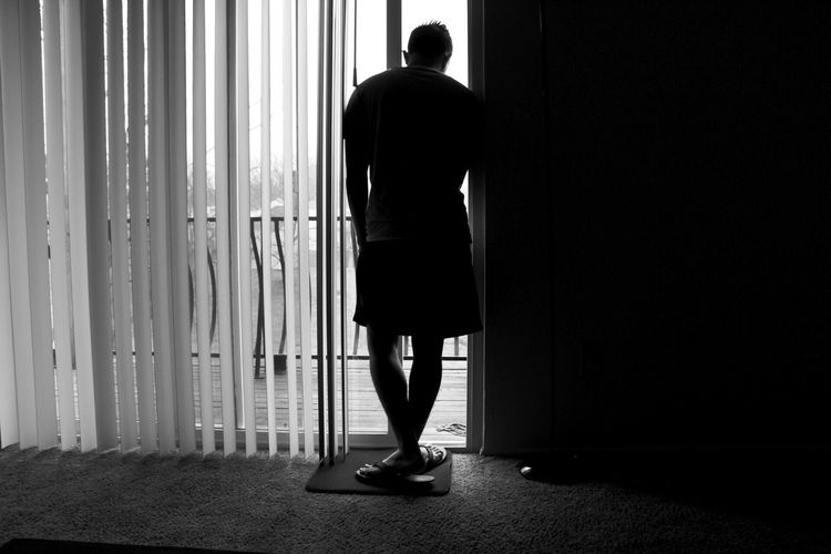 Full length rear view of silhouette man standing near window at home
