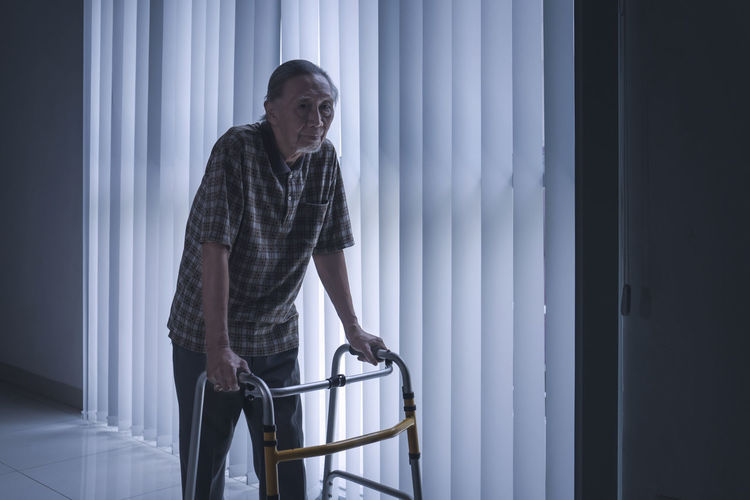 Disabled man walking by blinds with walker