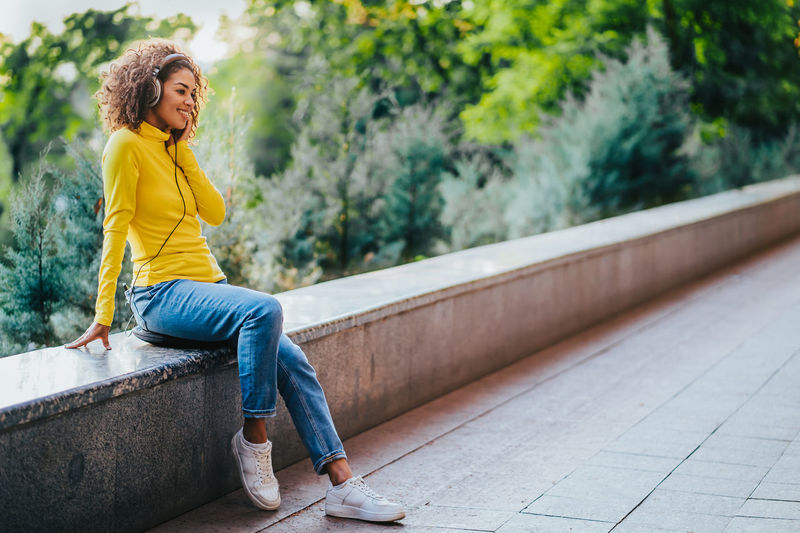 Full length of woman sitting on yellow looking away