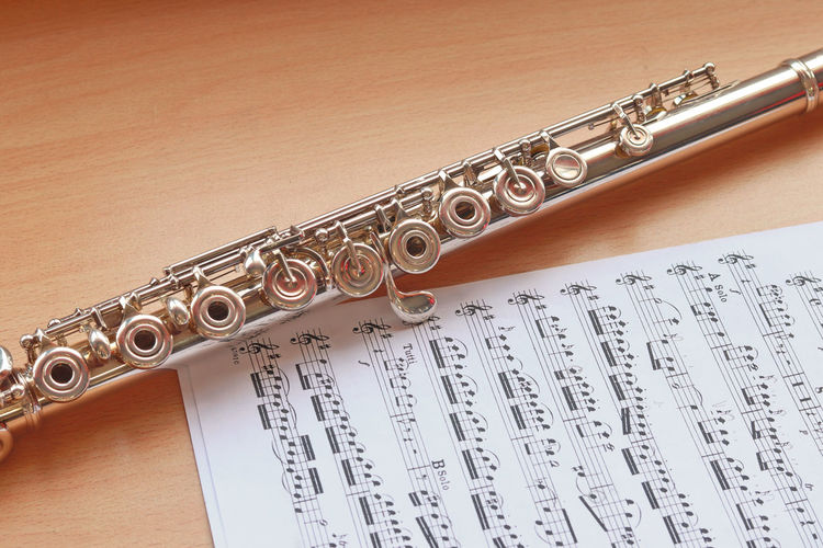 High Angle View Of Saxophone With Sheet Music On Wooden Table