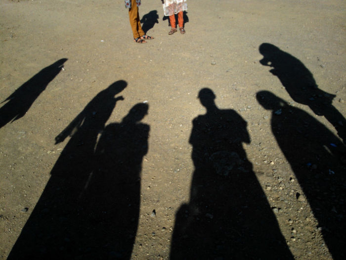 Shadow of people standing at beach