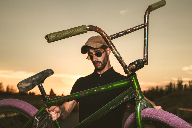Portrait of man holding bicycle against sky
