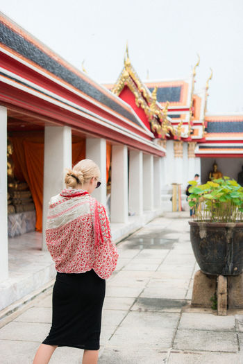 Rear view of woman standing outside temple against building
