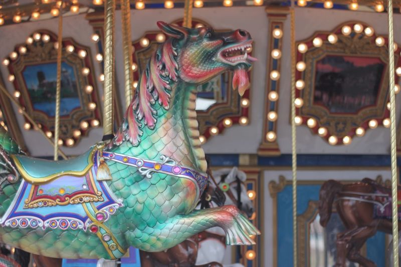 Dragon horse on a merry go round Horse Merry-go-round Colorful Dragon Representation Animal Representation Illuminated Carousel Amusement Park Ride No People Amusement Park Arts Culture And Entertainment Art And Craft Multi Colored Focus On Foreground Carousel Horses Decoration Animal Outdoors Creativity Holiday