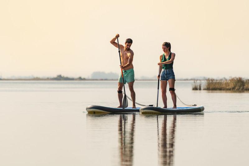 Full length of friends standing in lake against sky