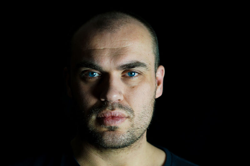 Portrait of serious man against black background
